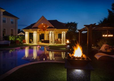 Outdoor pavilion with a bar and gas fireplace overlooking the pool